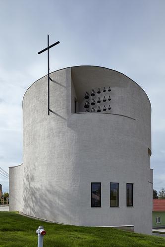 Pultová střecha se zvedá souběžně s terénem a kostel v nejvyšším místě vrcholí zvonicí a křížem.