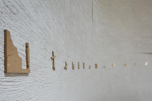 Minimalistický bronzový reliéf křížové cesty je v kontrastu s kartáčovanou omítkou, jež byla použita v interiéru i exteriéru.