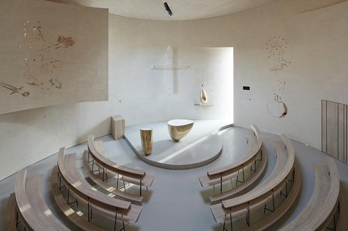 Interiér hlavní kruhové lodi je jednoduchý a čistý, výzdoba stěn se omezuje na bronzové reliéfní kresby; mensa, ambon a svatostánek jsou organického tvaru, s dokonalým povrchem z bronzu.