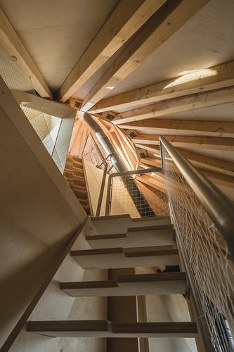 Vertikálně spojitý prostor pokračuje po strmých dřevěných schodech až do 3. NP; světlík v horním podlaží umožňuje pronikání jižního slunce celým domem.