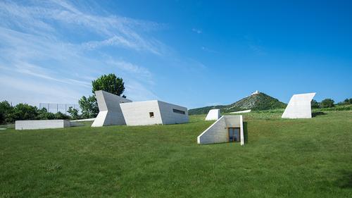 """Stavba je celá ukryta pod terénem, nad povrch vystupují pouze bílé prosvětlovací věže jako volná parafráze """"vápencových skal vybíhajících ze zeleně luk a vinohradů""""."""