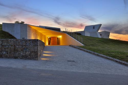 Nálevkovitě tvarovaný vstupní předprostor formují gabionové zdi a stěny z pohledového betonu.
