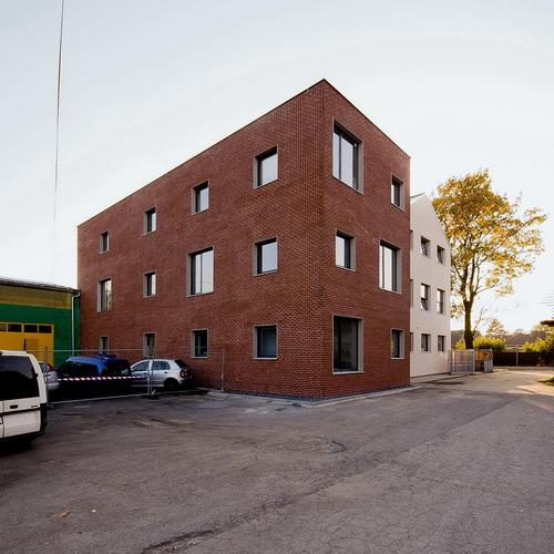 Přístavba vložená do proluky mezi původní budovou školy a hospodářskými objekty uzavírá areál bývalého hospodářského dvora; ze zadní strany jsou řešeny služební vstup a zásobování školní jídelny.