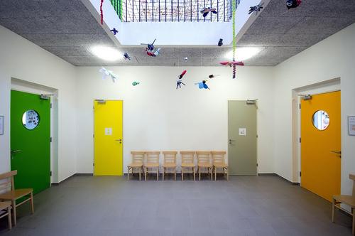 Barevný koncept se nejlépe uplatňuje v dvoupodlažním atriu přístavby, osvětleném střešním světlíkem, které je centrálním komunikačním prostorem školy.