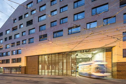 Pascal Müller, Samuel Thoma / Müller Sigrist Architekten: polyfunkční dům Kalkbreite v Curychu, dokončeno 2014; objekt vznikl na místě tramvajového depa, které bylo do budovy plně integrováno a doplněno třípodlažním městským parterem a