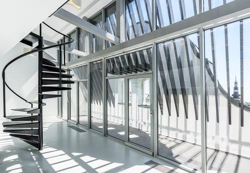 Převýšený prostor v 5. NP; vložení svislé skleněné stěny umožnilo vytvoření venkovní terasy, hliníkové lamely jsou osazeny v původní rovině střechy a zachovávají její tvar v pohledu z náměstí.