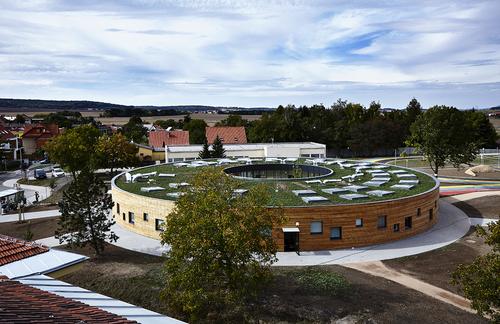 Pavilon základní školy v Líbeznicích u Prahy je určen pro 240 dětí v osmi kmenových učebnách; vnější fasáda rondelu je zděná s obkladem z nehoblovaných modřínových prken a nepravidelně rozmístěnými okenními otvory, fasáda do atr