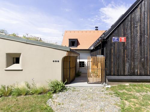 Dům A1, pohled z ulice Hostavické: nová hmota svou kontrapozicí posiluje a zvýrazňuje charakteristické podélné postavení okolních domů; ve svém kontrastu je důsledná, a tak není zděnou uzavřenou hmotou, ale otevřeným dřevěným domem;