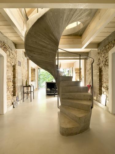 Subtilní betonové točité schodiště umístěné na křížení obou domů stoupá směrem vzhůru, kde se kříží i obě sedlové střechy.