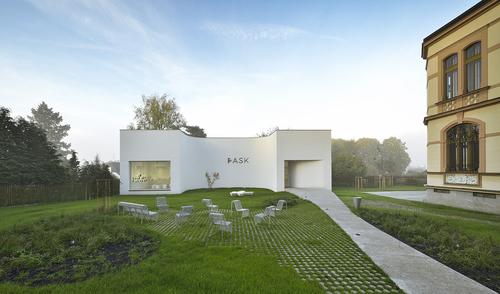 Pavilon skla Klatovy – PASK, pohled z ulice Hostašovy: organická křivka chodníku zdůrazňuje asymetrické umístění hlavního vstupu, do budoucna se počítá s umístěním některých exponátů v prostoru zahrady; jednopodlažní zděná stavb