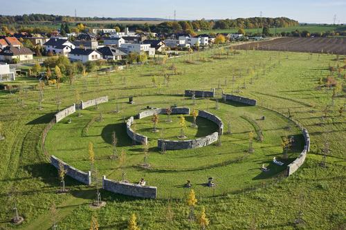 Park o rozloze čtyř hektarů je doplněn stromy v rozvolněném rastru, keři, květnatými loukami a štěrkovými cestami; spojení kříže a kruhu odkazuje na rovnováhu a harmonii.