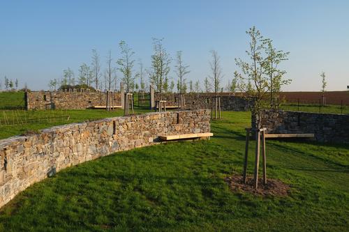 Střed hřbitova s kruhovými kamennými zdmi.