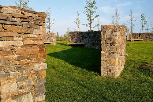Kruhové zdi s dřevěnými lavičkami vytvářejí zákoutí k odpočinku.