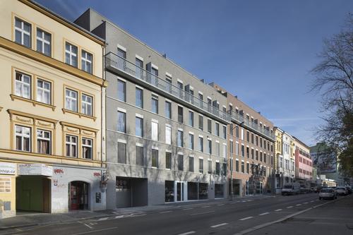 Pohled zulice Koněvovy; proporce oken domu se přizpůsobují tradičním rozměrům otvorů typických pro původní zástavbu vokolí; výrazným prvkem na čelní fasádě je dlouhý vysunutý balkon v5.NP.