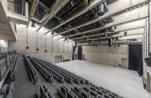Víceúčelový sál mění své akustické vlastnosti pomocí otočných panelů na stropě, vysunutím či složením hlediště apropojením sfoyery.