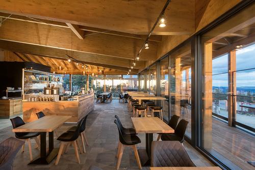 Samoobslužná restaurace vhorním podlaží je ze tří stran prosklená aposkytuje výhled na panorama Beskyd; pocit prostoru umocňuje otevření do krovu.
