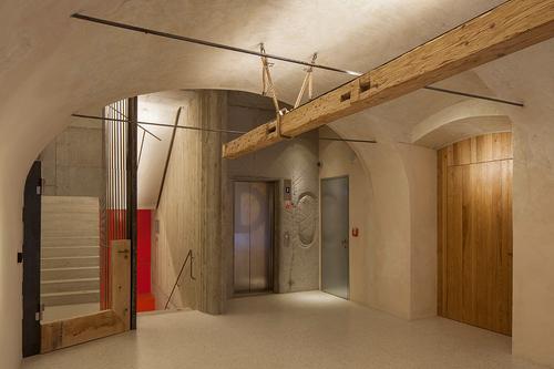 """Do novostavby jsou přeneseny různé prvky způvodního barokního paláce; sám autor tento přístup nazývá """"restaurátorským brutalismem""""."""
