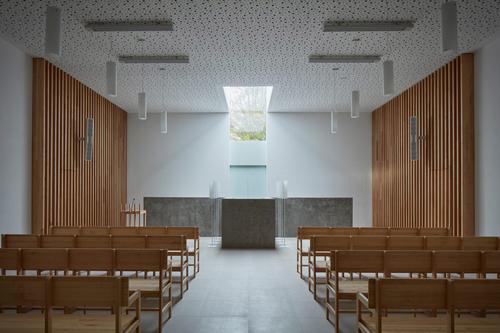 Převýšený prostor smuteční síně je prosvětlen jediným oknem; interiér kombinuje světlé barvy sjasanovým dřevem acementovou stěrkou.