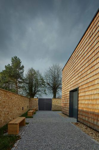 Odsazení obvodového zdiva definuje intimní prostor dvora před vstupem do samotného sálu.