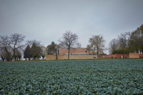 Nová smuteční síň prodlužuje linii hřbitovní zdi astává se součástí panoramatu vpodhůří Orlických hor.