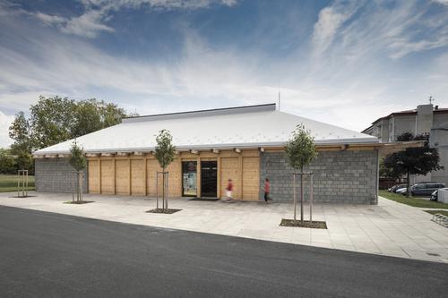 Předprostor prodejny na okraji sídliště doplňuje čtveřice sakur; objem stavby vymezuje dvojice pylonů vyzděných zbetonových tvárnic, na nichž leží valbová střecha tvořená příhradovou konstrukcí.