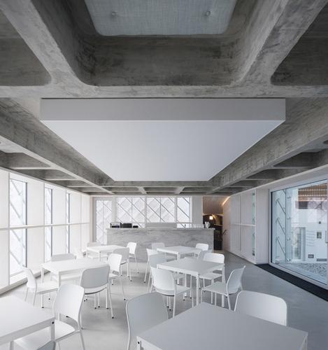 Skleněný dům je srdcem firmy, funguje zároveň jako kavárna ajednací prostor.