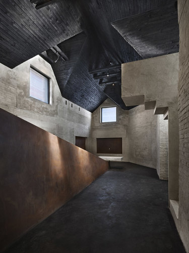 """Interiérem vesnického domu, zbaveného původních vnitřních konstrukcí apřetvořeného kvnímání místa vrovině symbolické, proniká """"hranazla"""" azaráží se do desky rodinného stolu, tak jako se zlo vlomilo do života rodiny-"""