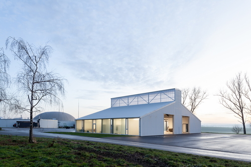 Opláštění budovy dílen zbílého trapézového plechu je obdobné jako usousední bioplynové stanice, která celému areálu dominuje.