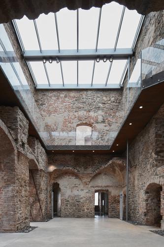 Mezi přesnými deskami chodníků zhlazeného betonu anepravidelnými stěnami paláce byl ponechán odstup; plochu vyplňuje kamenivo, které smiřuje nepravidelnost snekompromisní rovnou linií.