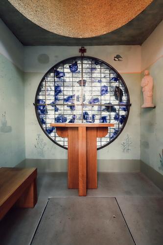 Nejvýraznějším prvkem interiéru je kruhová rozeta vyskládaná barevnými skleněnými střepy, zevnitř doplněná subtilním kovovým křížem; foto: Matěj Chabera.